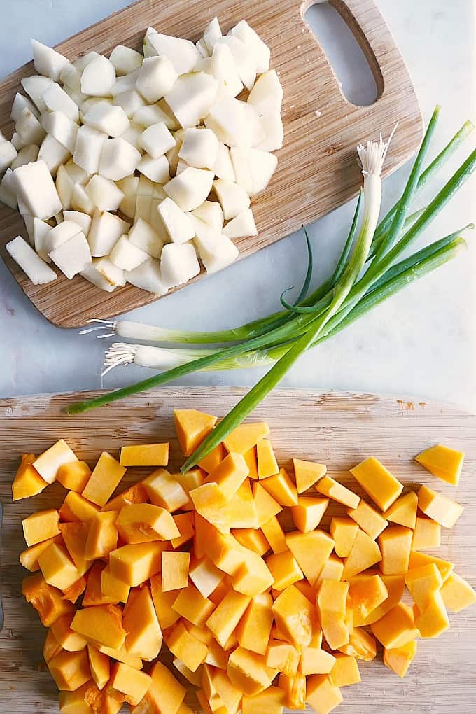 chopped butternut squash and pears on two cutting boards with leeks in between them