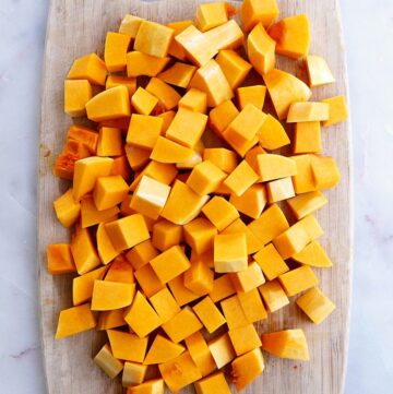 butternut squash cubes spread out on a cutting board on a counter