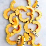 delicata squash cut into half-moon shapes spread out on a white counter
