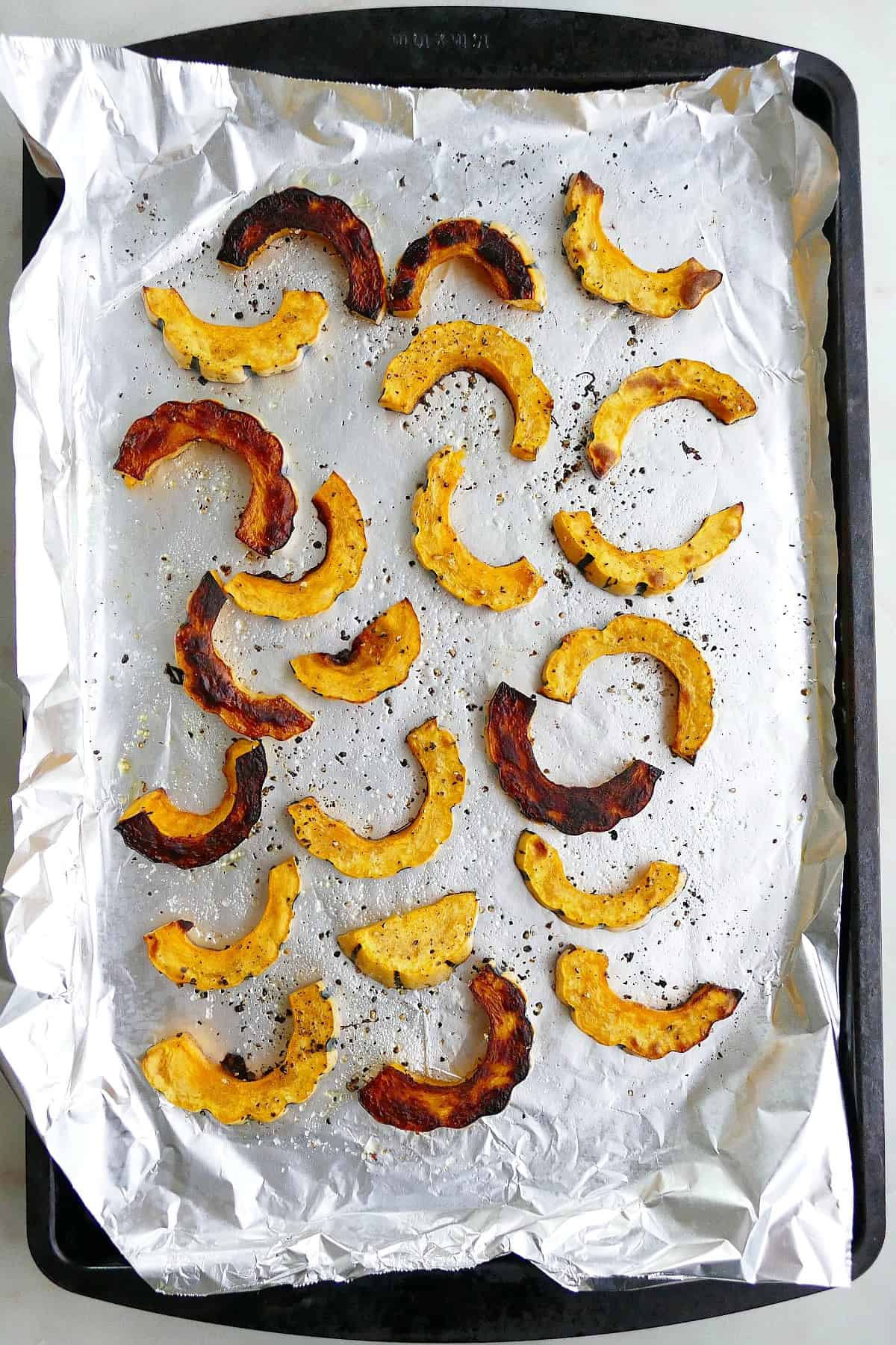 baked delicata squash fries on a baking sheet lined with aluminum foil