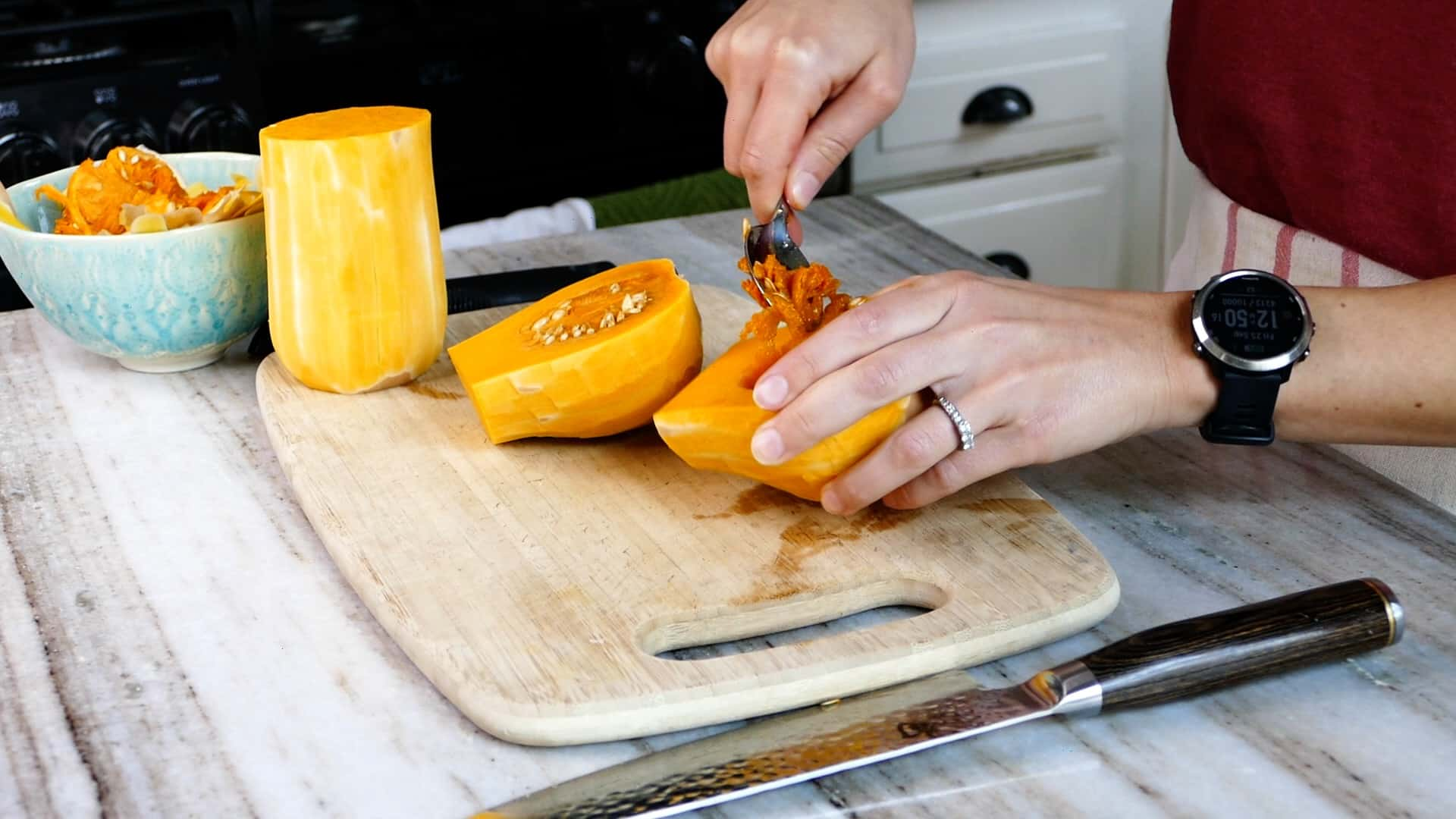 woman scooping out seeds from the base of a butternut squash