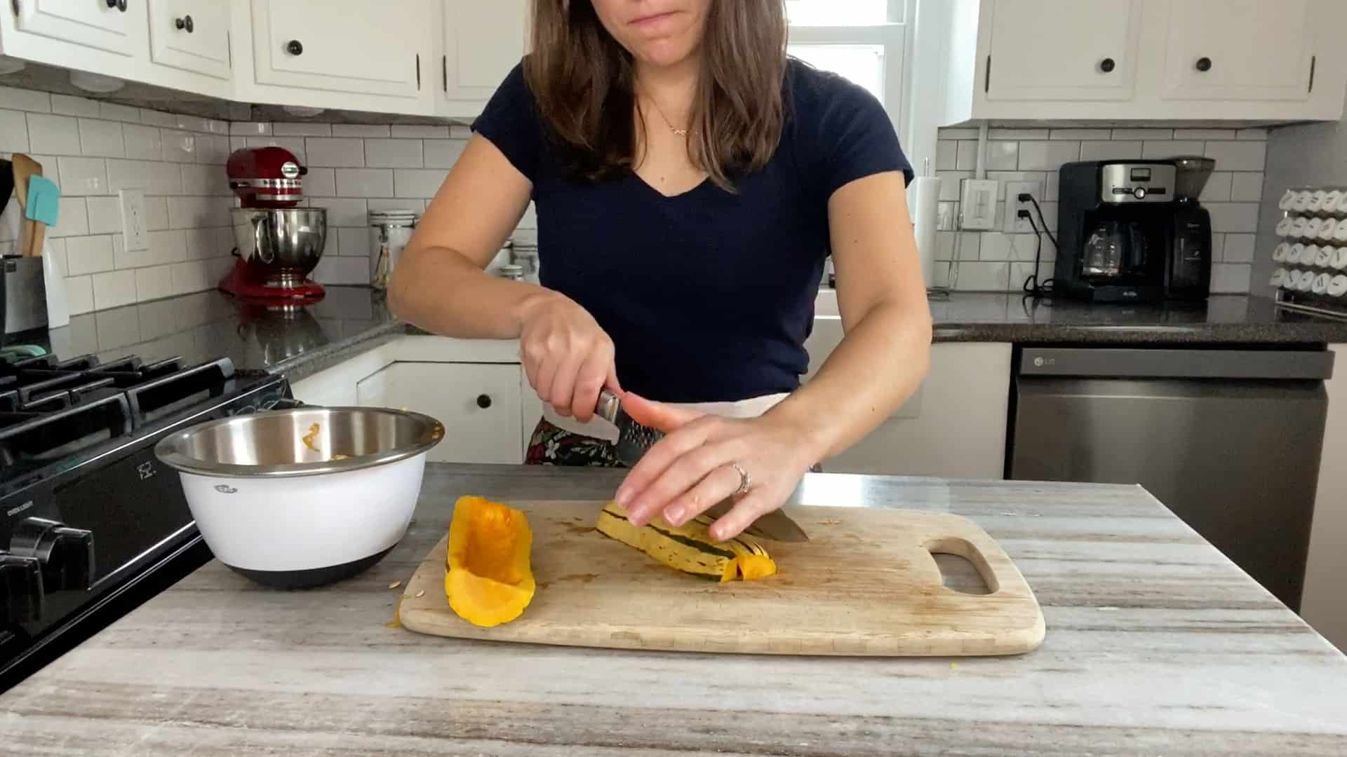 woman cutting delicata squash into pieces on a cutting board