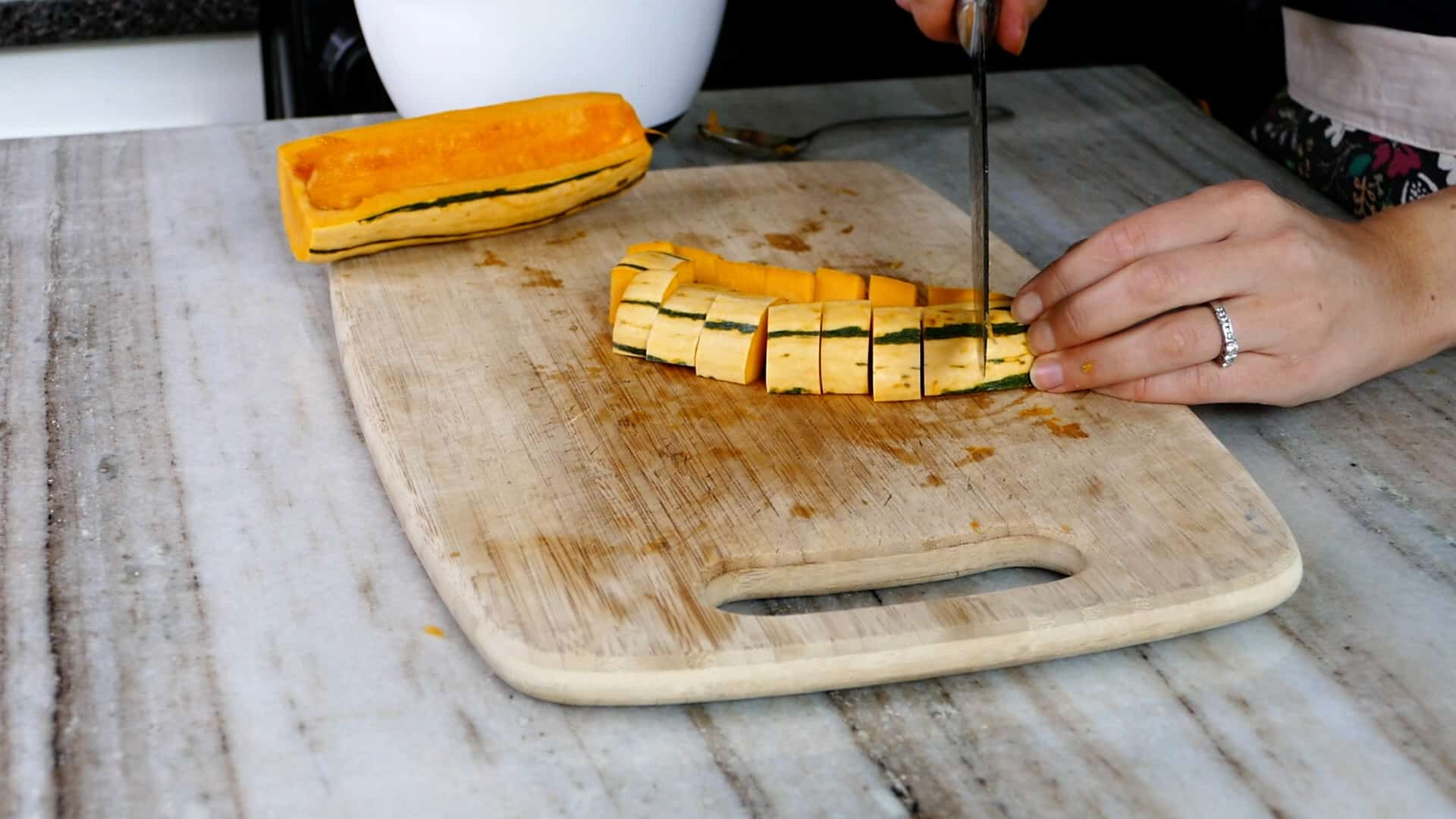 woman's hand cutting delicata squash into cubes on a cutting board