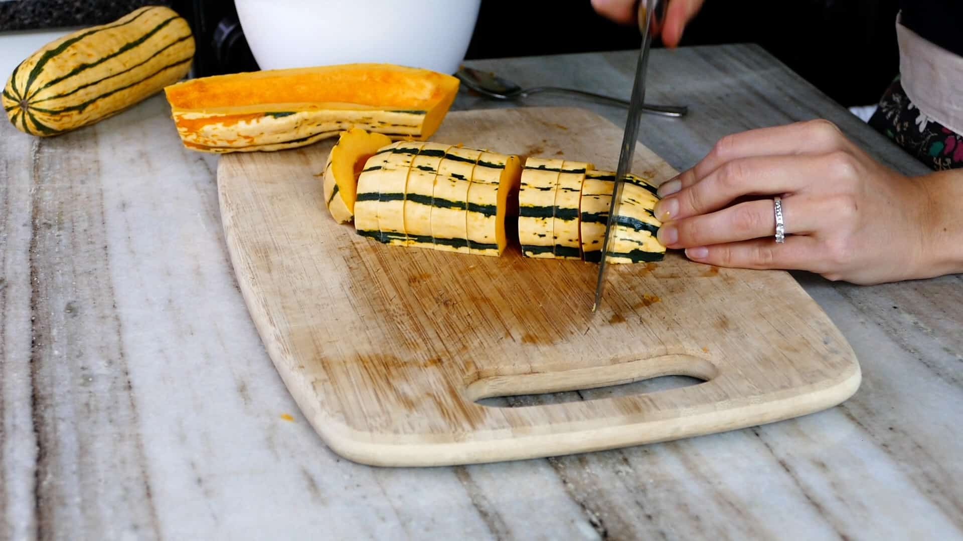 woman's hand cutting delicata squash into fries on a cutting board