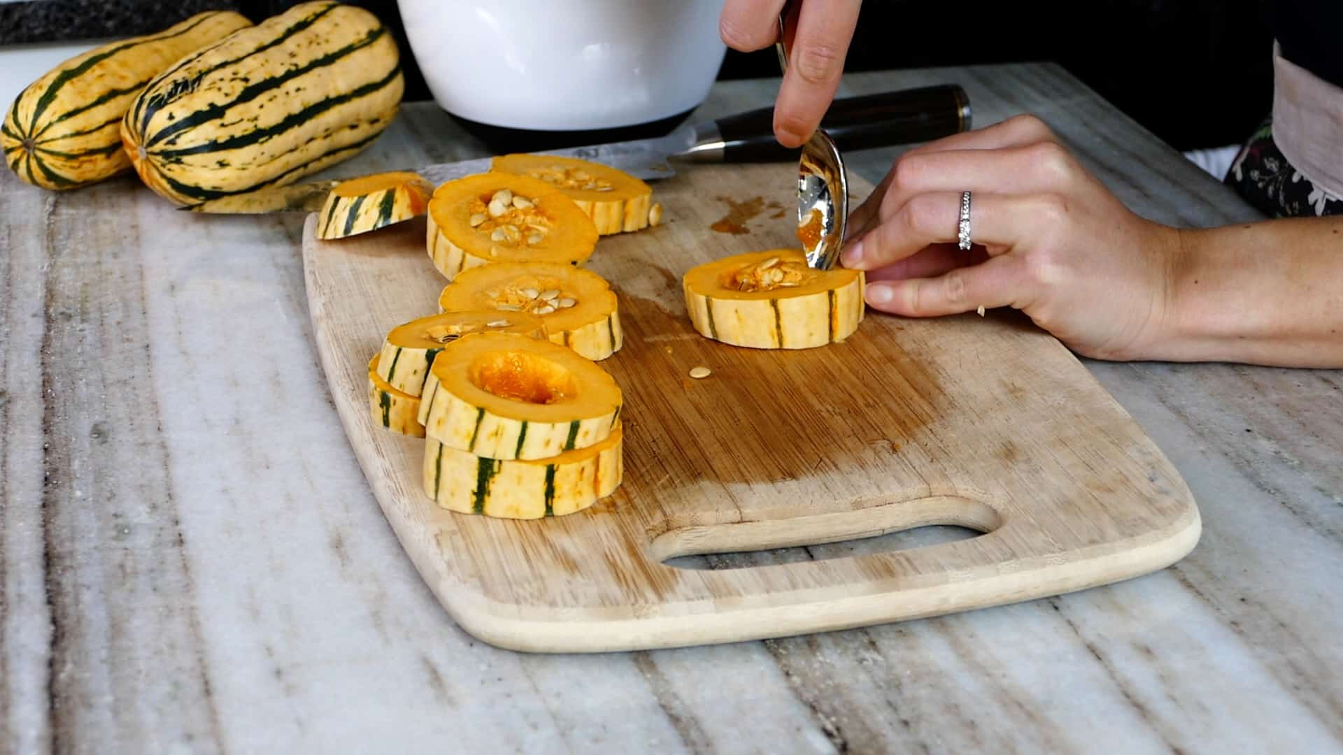 woman scooping out seeds from delicata squash rings on a cutting board