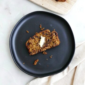 square image of a slice of pumpkin oatmeal bread on a black plate on a counter