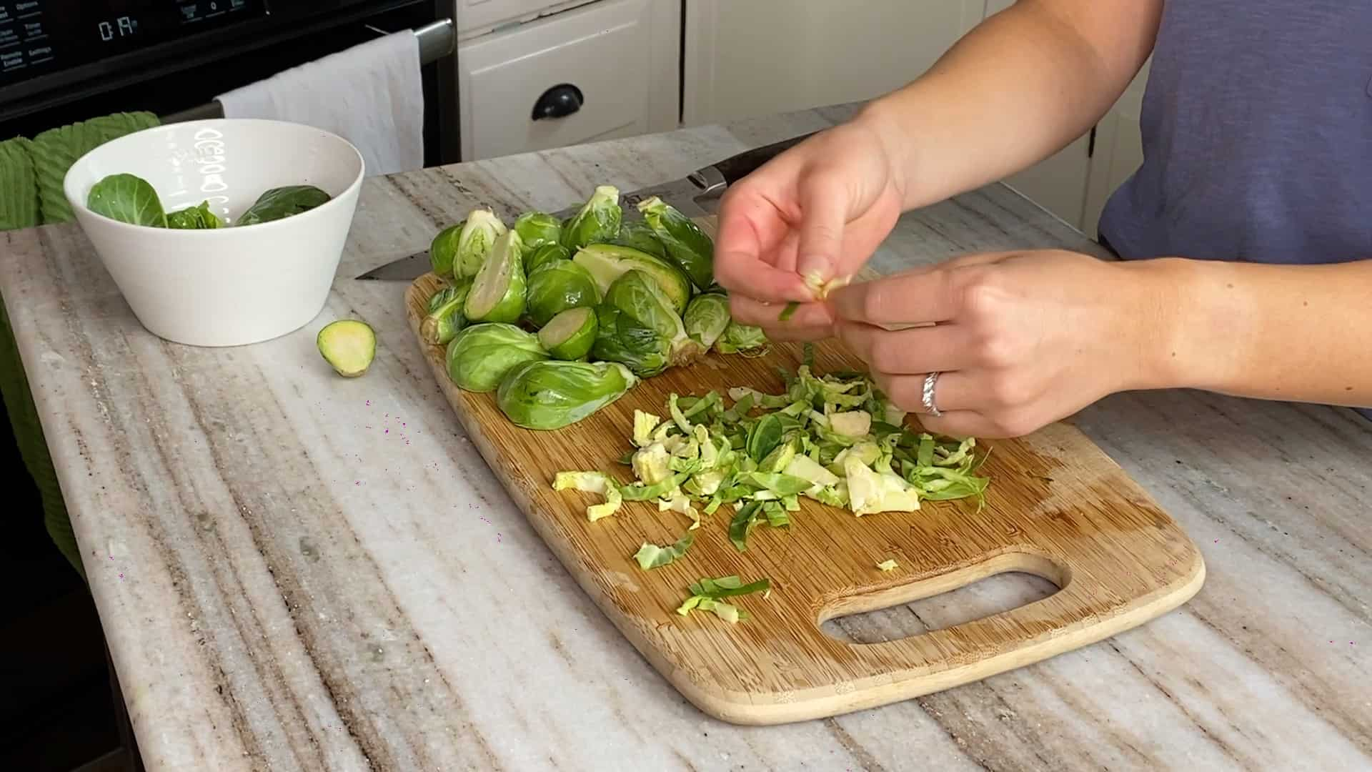 woman peeling apart shredded brussels sprouts with her fingers over a cutting board