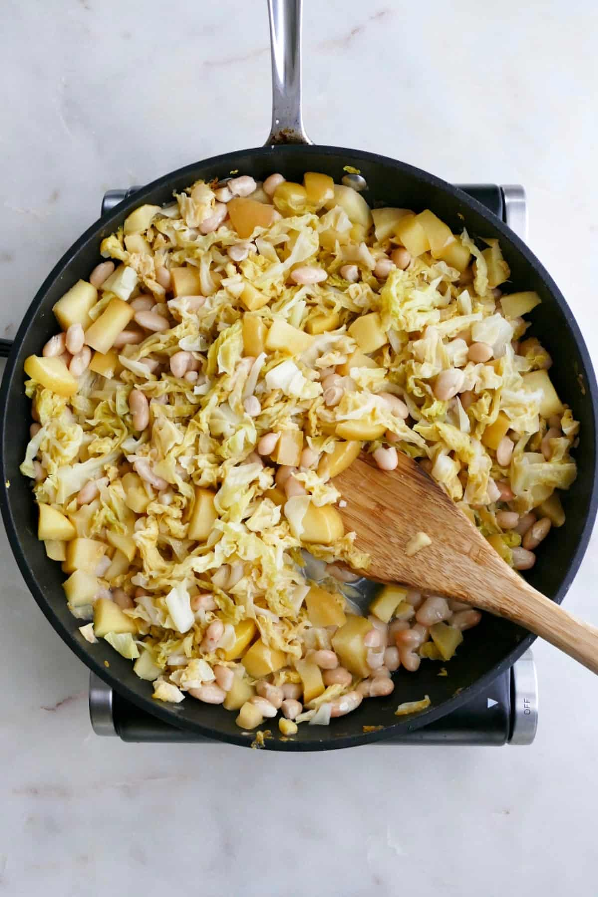 stewed cabbage, apples, and white beans in a large skillet with a wooden spoon