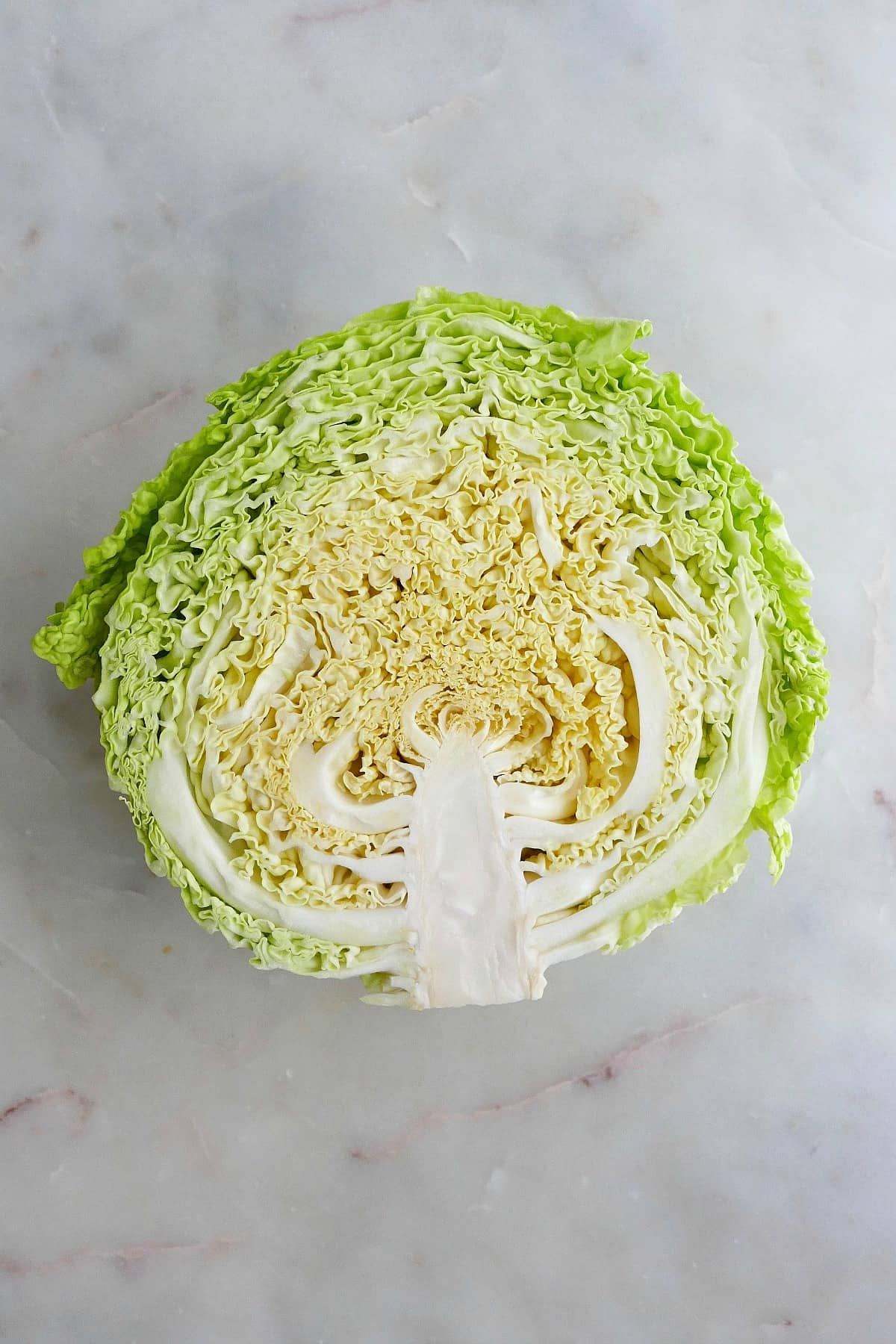 half of a head of savoy cabbage cut side up on a counter