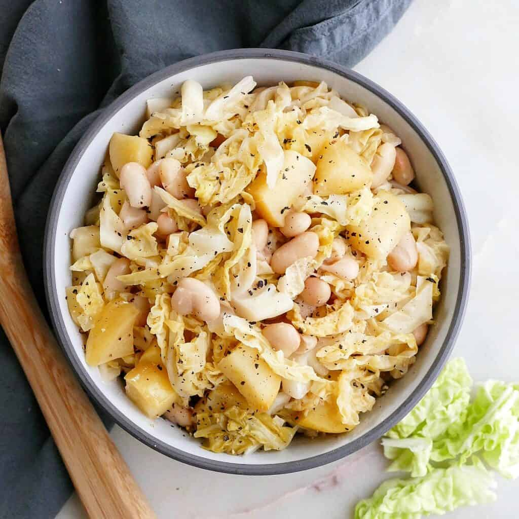 square image of stewed cabbage, apples, and white beans in a serving bowl