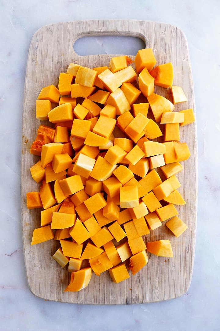 butternut squash cubes spread out on a bamboo cutting board on a counter