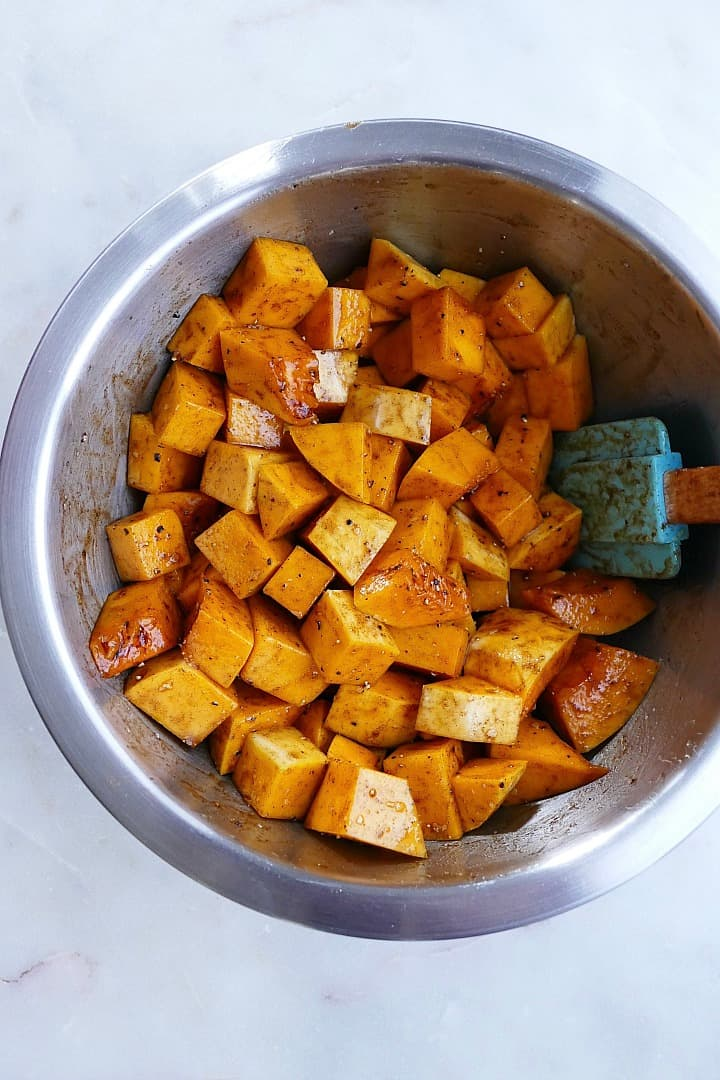 butternut squash cubes tossed in cinnamon and maple syrup in a mixing bowl
