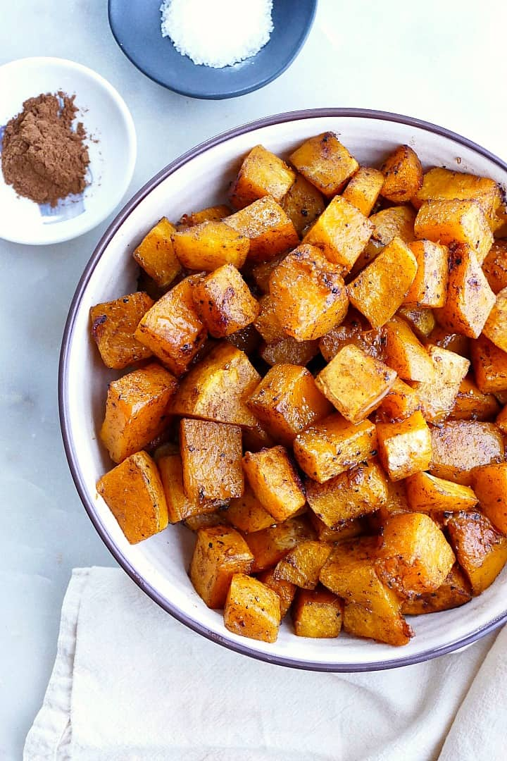 close image of roasted butternut squash in a serving bowl on a counter