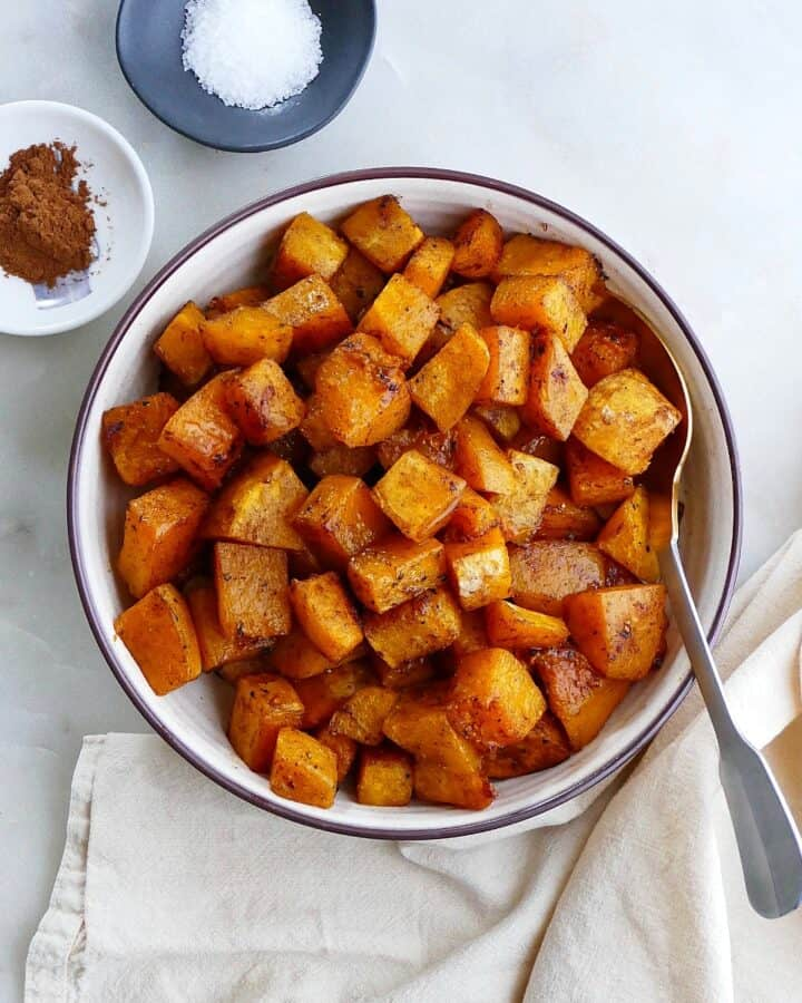 square image of cinnamon roasted butternut squash in a serving bowl on a counter