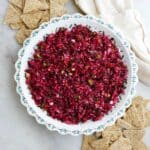 cranberry jalapeno dip in a serving dish next to triscuit crackers on a counter