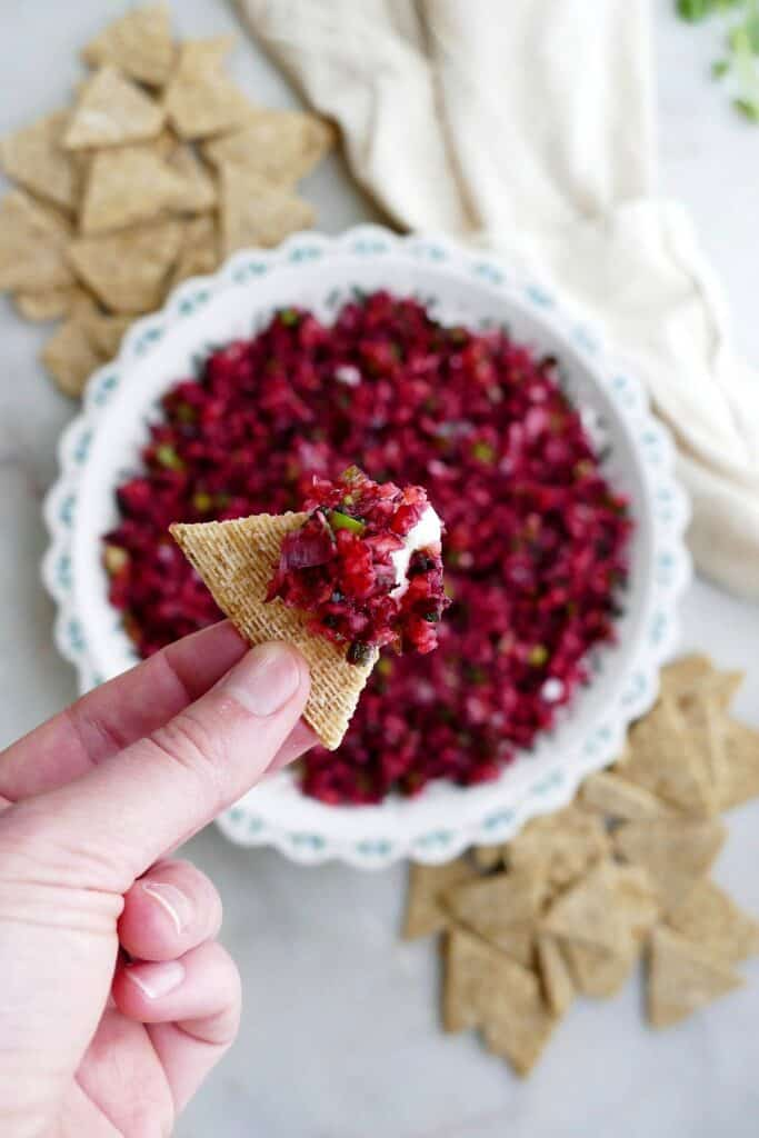 a hand holding a cracker with cranberry jalapeno cream cheese dip over a counter