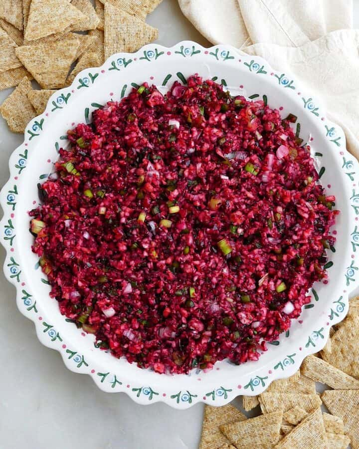 square image of cranberry jalapeno dip in a serving dish next to crackers on a counter