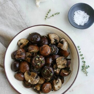 serving bowl with garlic roasted mushrooms next to garlic bulbs, thyme, and salt