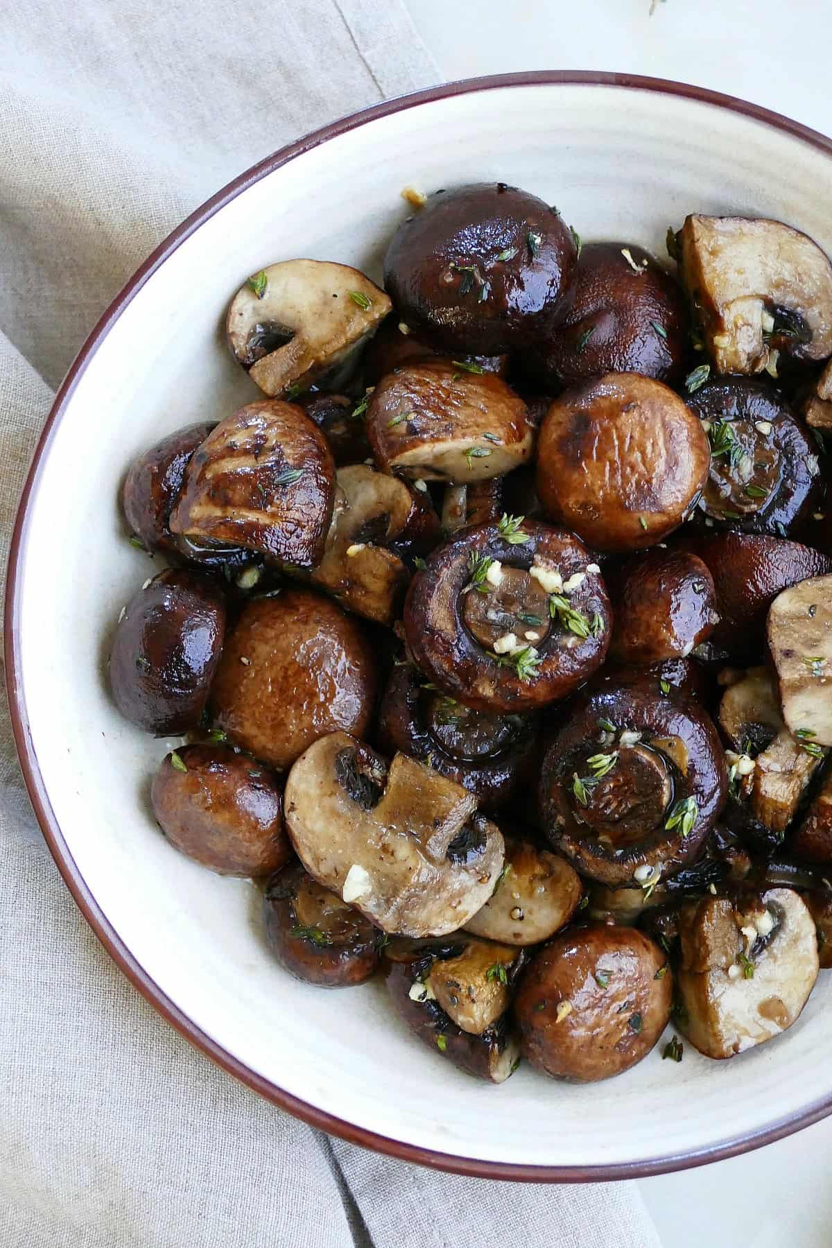 close-up image of garlic roasted mushrooms with thyme in a serving bowl on a counter