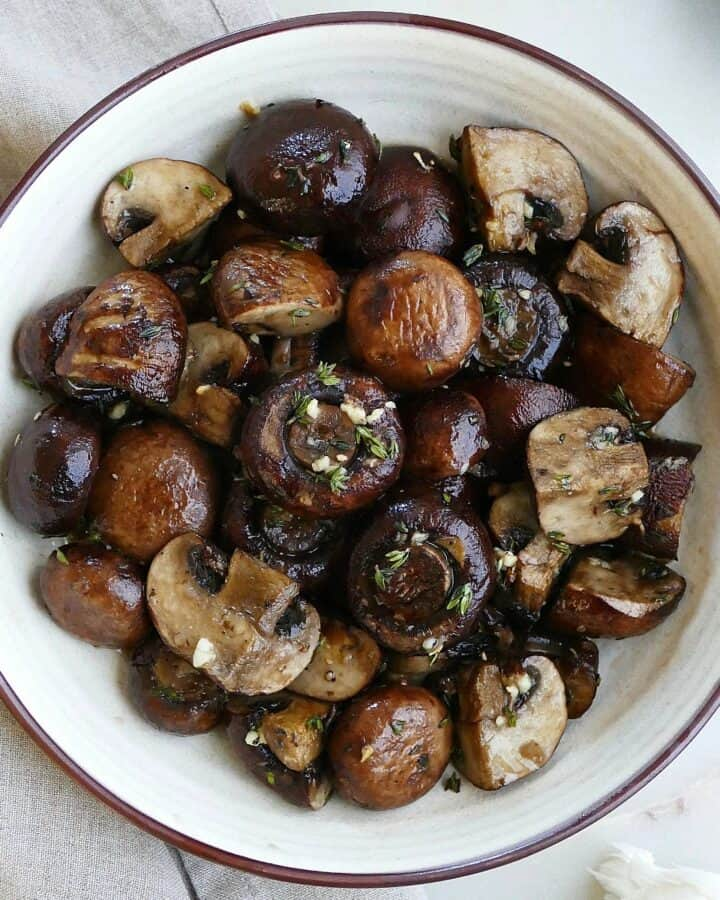 square image of garlic and thyme roasted mushrooms in a serving bowl on a counter