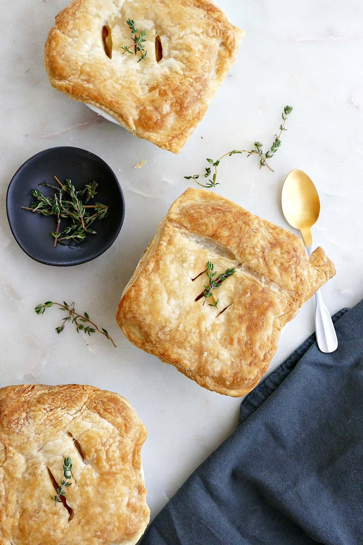 three individual pot pies with thyme sprigs on a counter next to each other