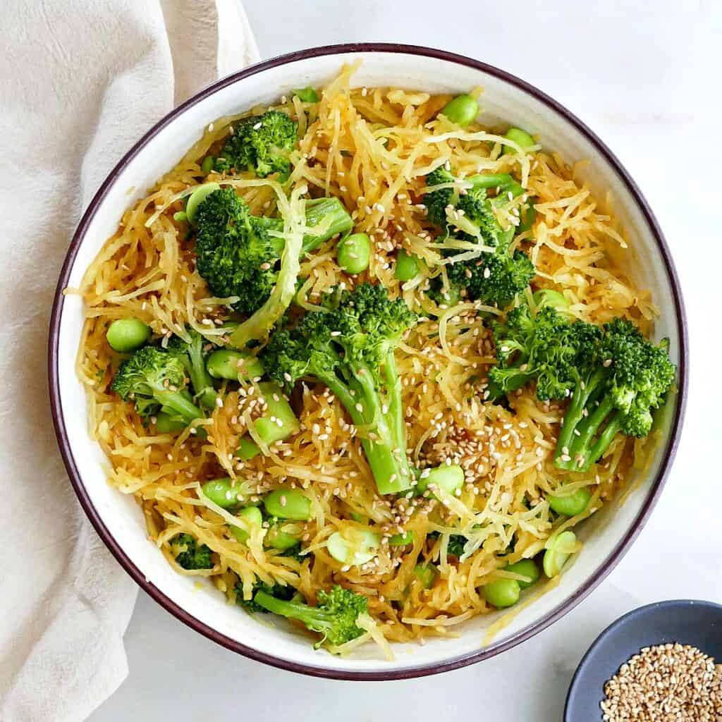square image of spaghetti squash stir fry with edamame and broccoli in a serving bowl on a counter