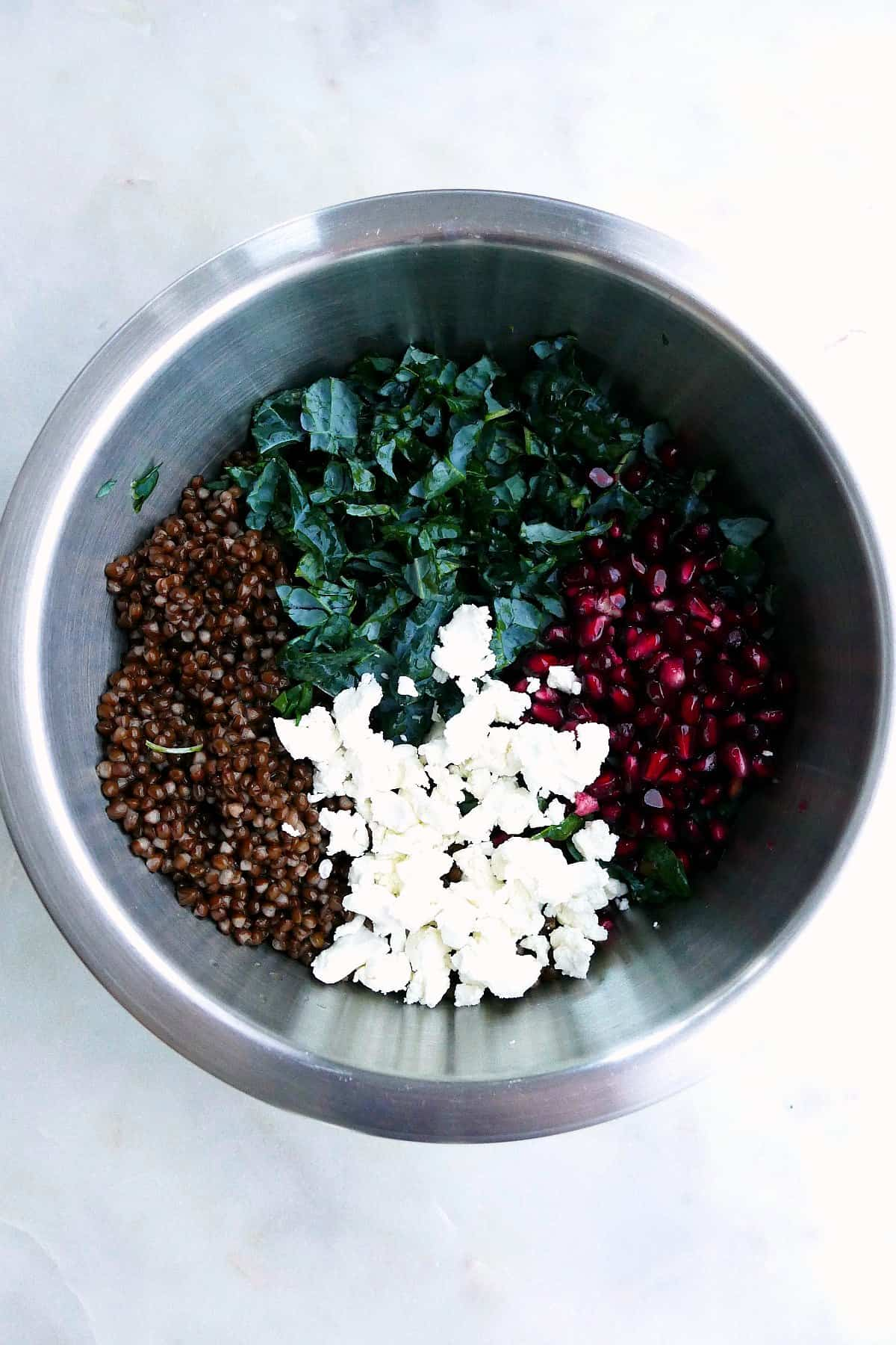 black lentils, finely chopped kale, goat cheese crumbles, and pomegranate arils in a bowl