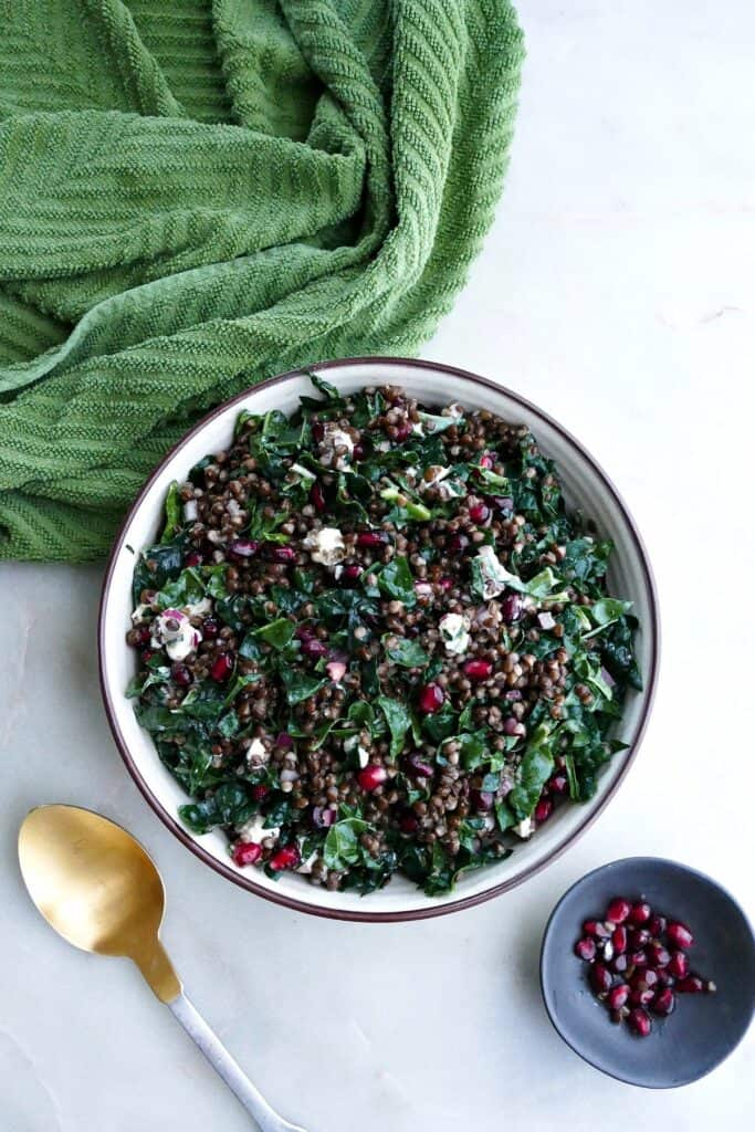 black lentil and kale salad in a serving bowl next to a napkin and spoon