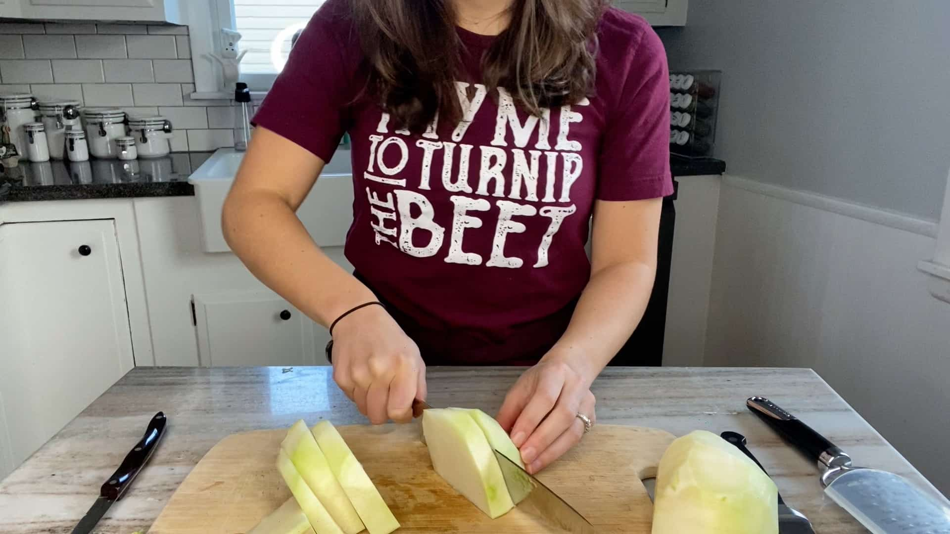 photo of a woman slicing a green kohlrabi into thick round slices
