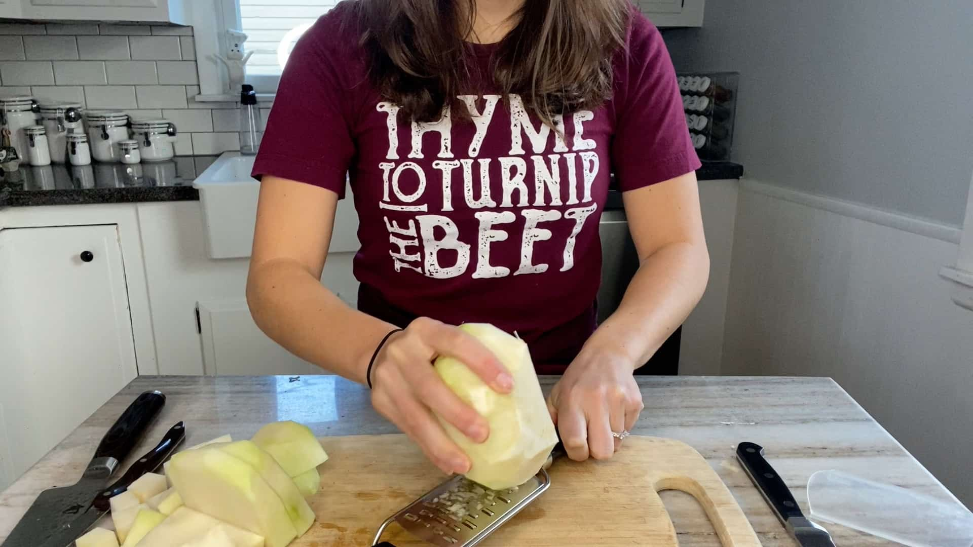 photo of a woman grating half of a peeled kohlrabi over a cutting board