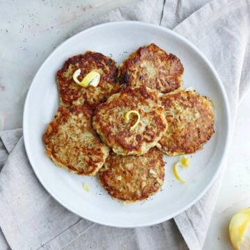 six kohlrabi fritters topped with lemon zest on a serving platter