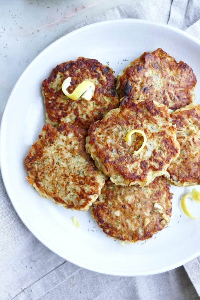 close-up image of kohlrabi fritters with lemon zest on a serving plate