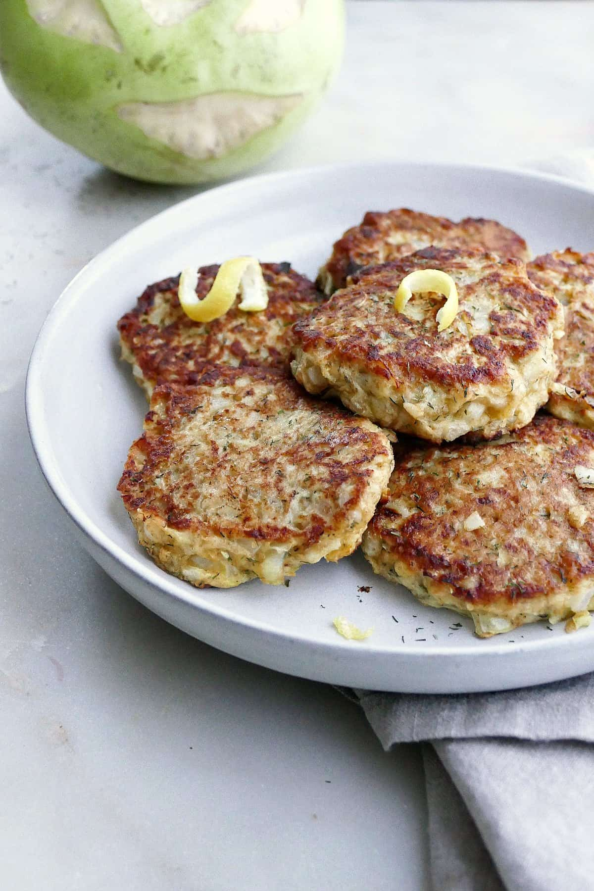 side image of kohlrabi fritters on a platter in front of a raw kohlrabi