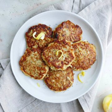 square image of six kohlrabi fritters topped with lemon zest on a serving platter