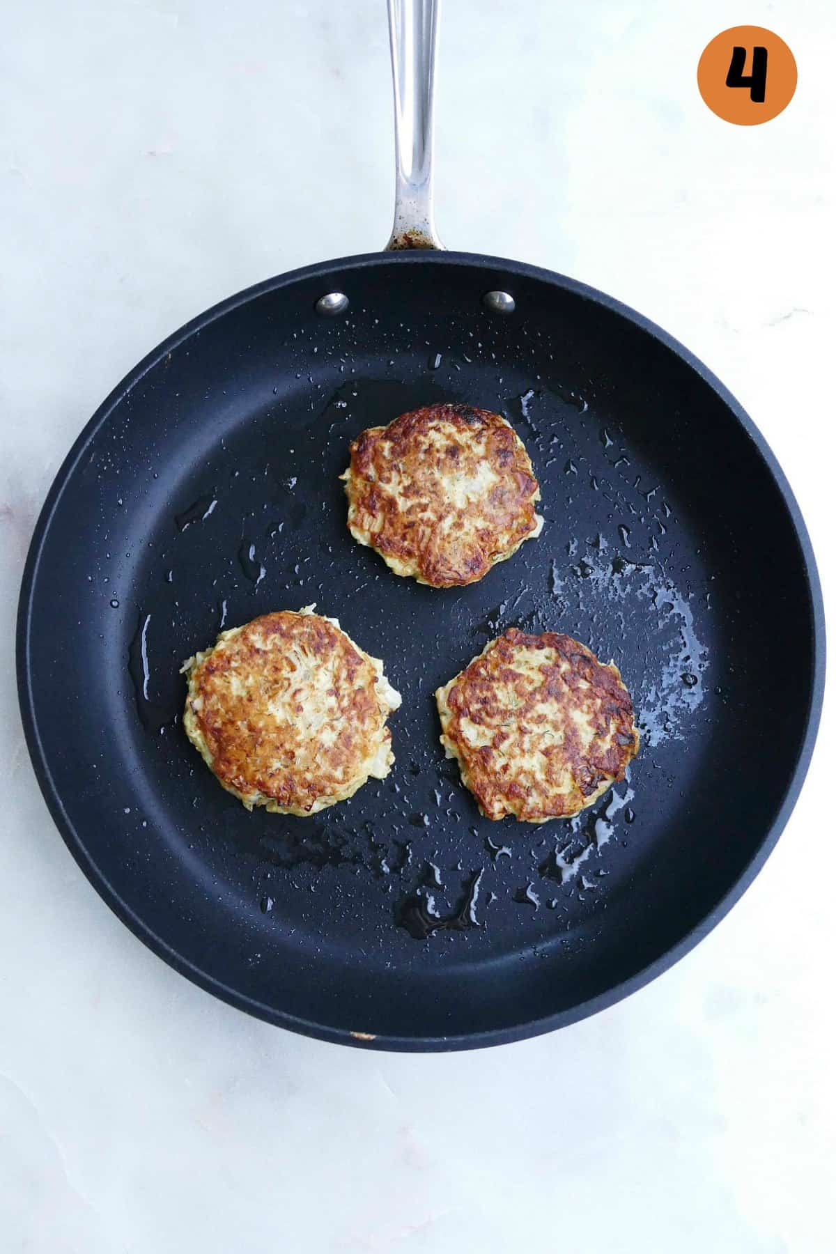 three kohlrabi fritters in a large black skillet on a counter