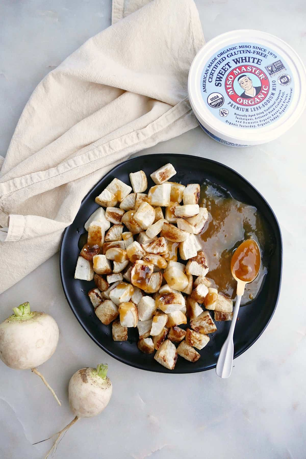 serving plate with roasted turnips and maple miso butter next to ingredients on a counter