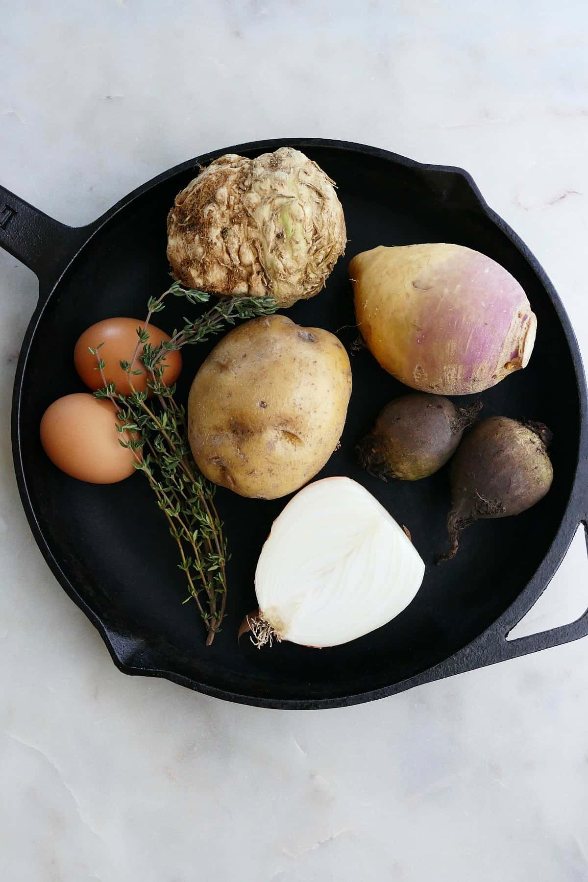 celeriac, potato, rutabaga, onion, beets, thyme, and eggs in a skillet