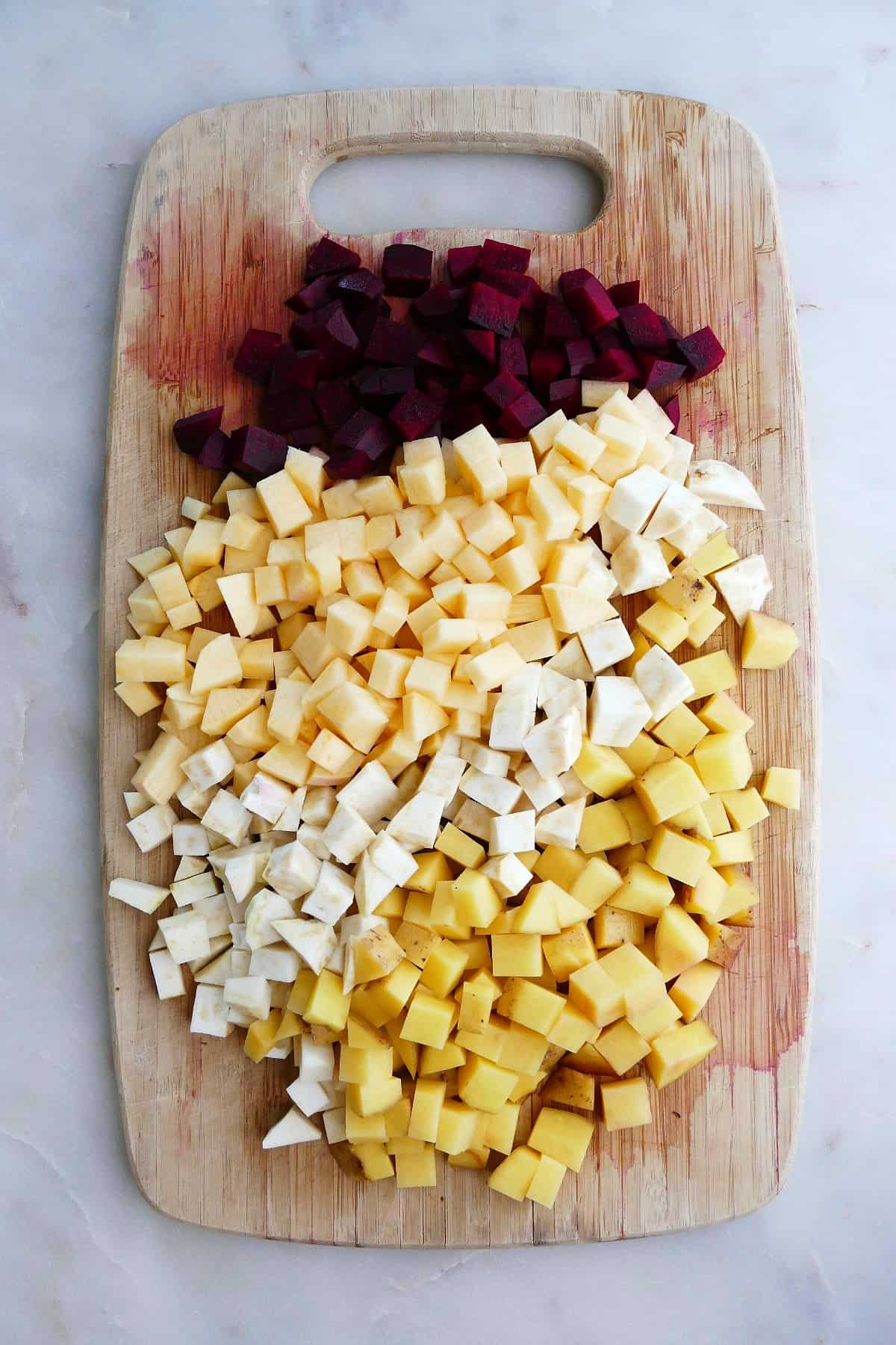 diced root vegetables spread out on a bamboo cutting board on a counter