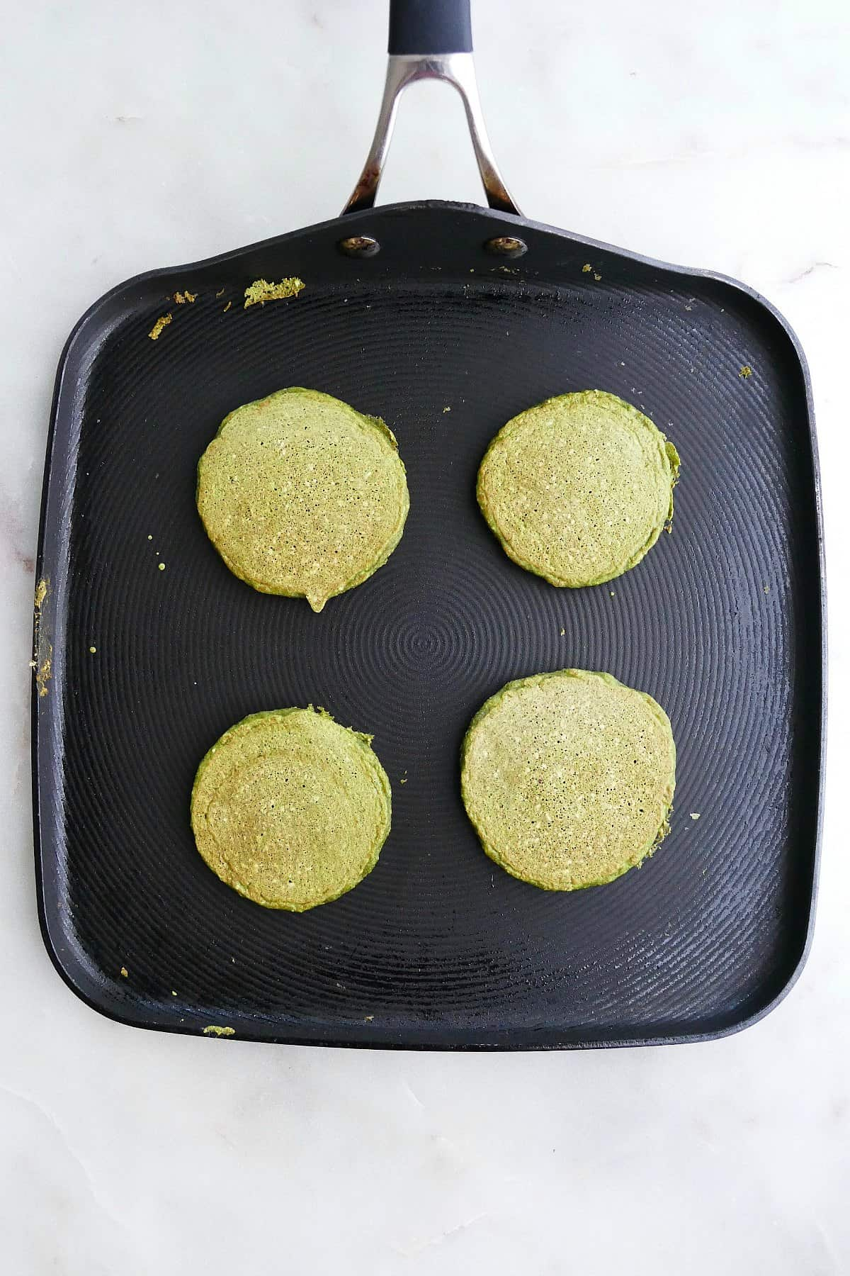 four spinach pancakes on a skillet on a counter