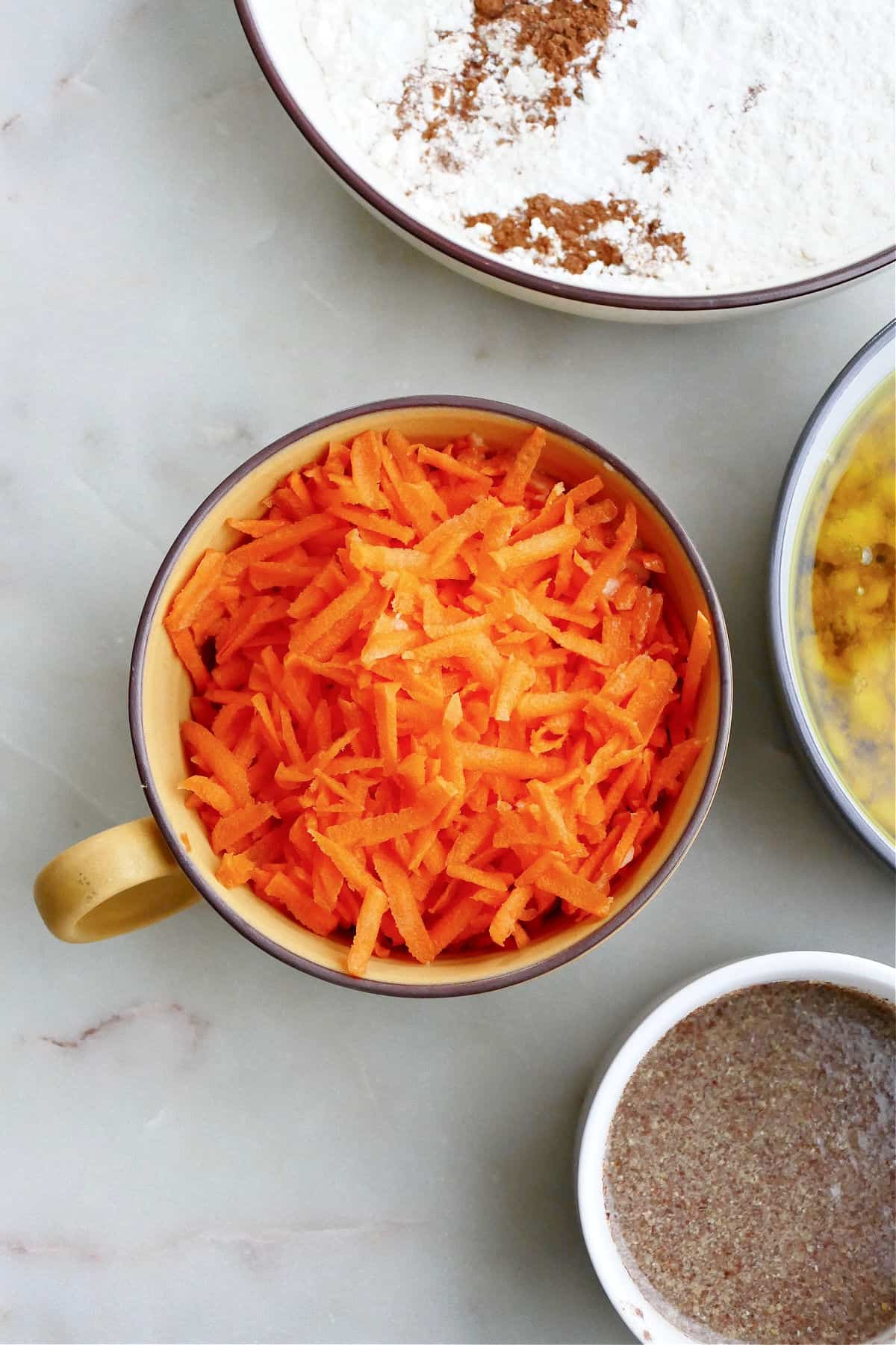 shredded carrots in a large mug next to other ingredients on a counter