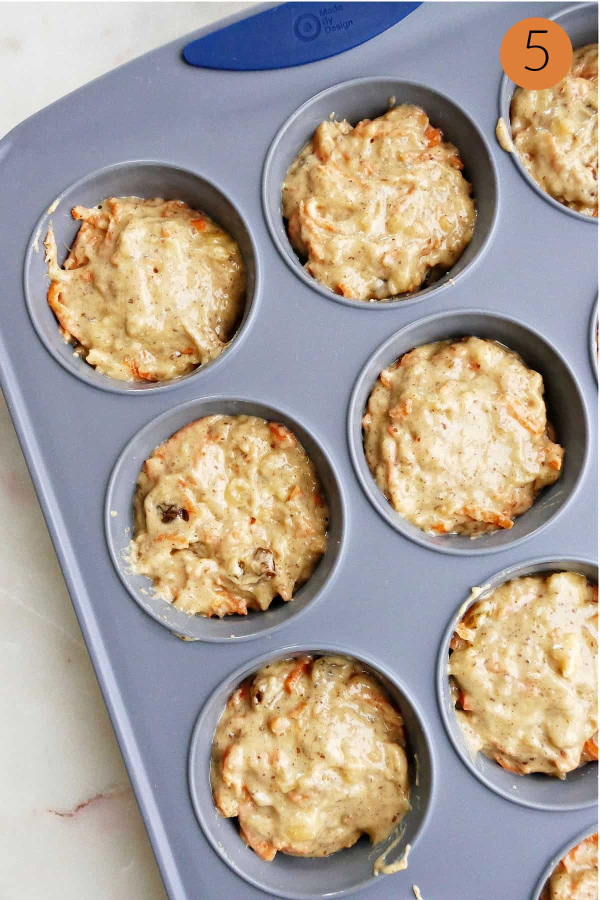 half of a muffin pan filled with batter for banana carrot muffins