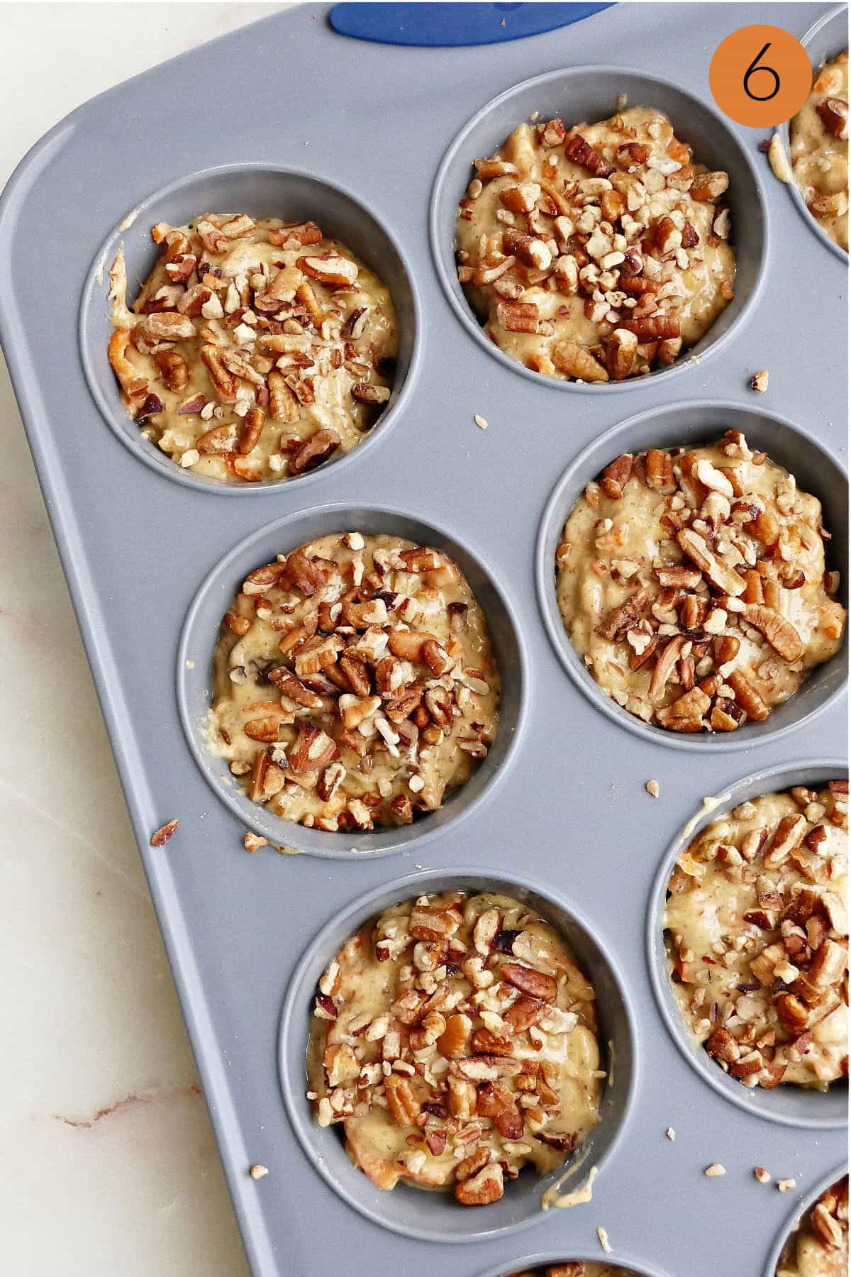 half of a muffin pan filled with batter and topped with chopped pecans