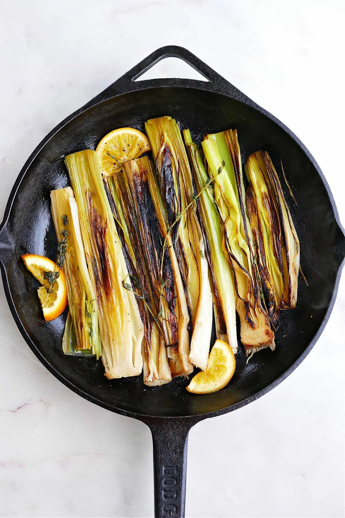 caramelized leeks in a cast iron skillet next to orange slices and thyme sprigs