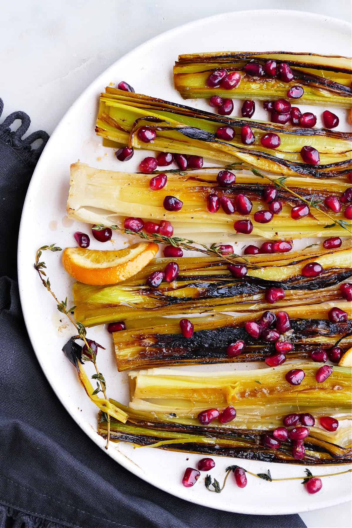 caramelized leeks with orange ginger pomegranate relish on a platter on a counter
