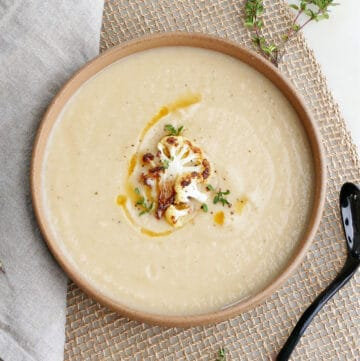 cauliflower and parsnip soup in a serving bowl topped with cauliflower, thyme, and oil