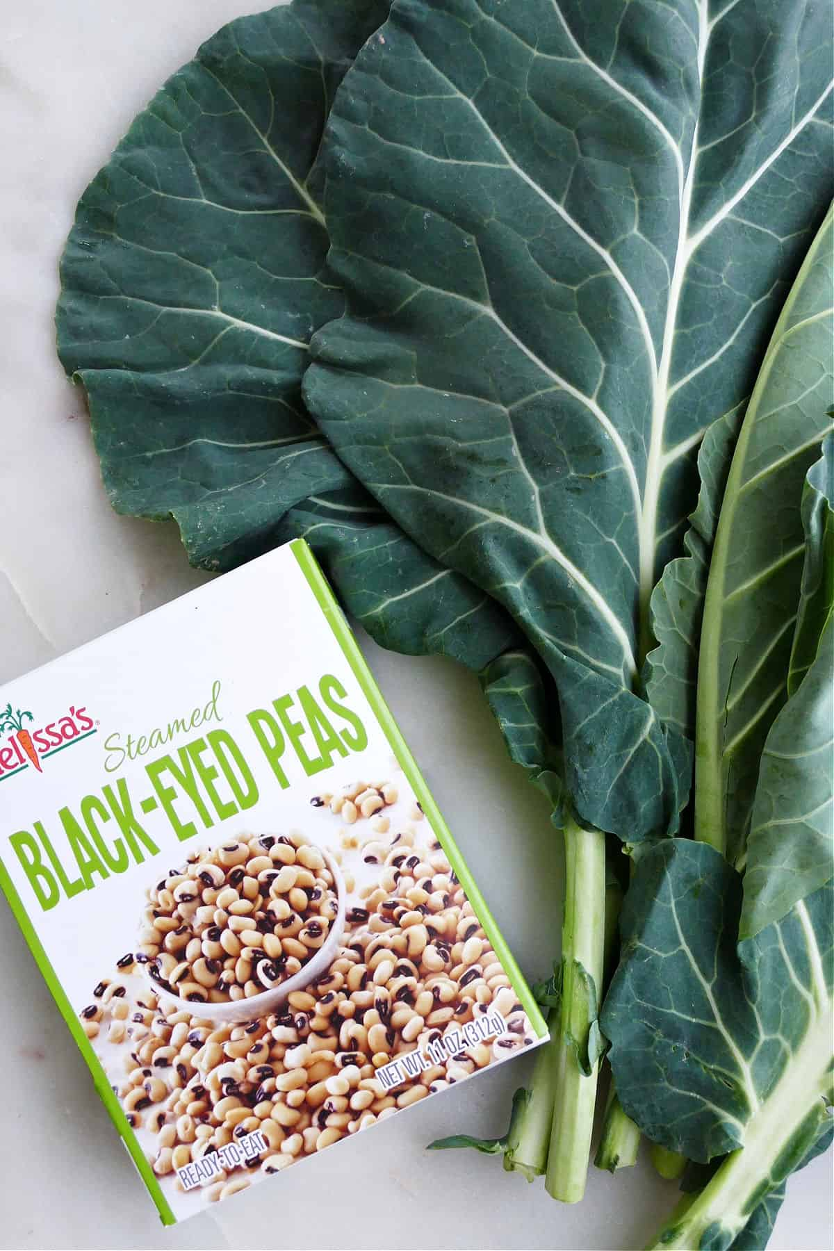 a box of steamed black eyed peas next to a bunch of collard greens on a counter