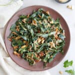 collard greens salad with peanut dressing on a brown serving dish on a counter
