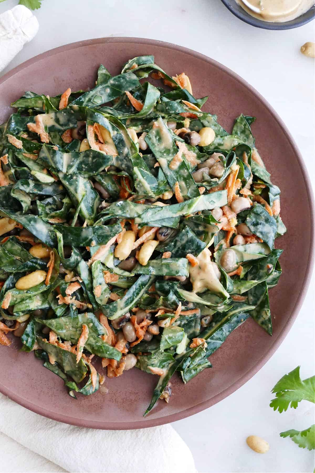 shredded collard greens, carrots, and peanuts with dressing on a brown serving dish