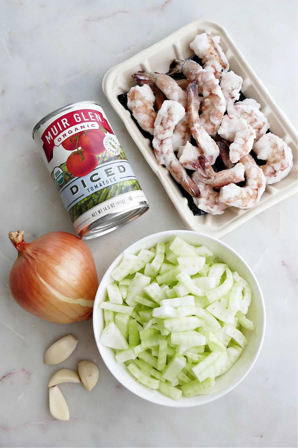 frozen shrimp, canned tomatoes, onion, garlic, and chopped fennel on a counter