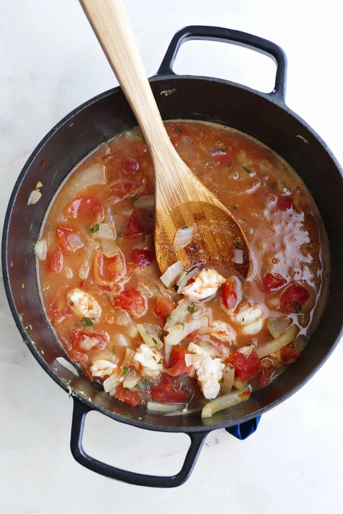 fennel stew with tomatoes and shrimp in a black pot with a wooden spon